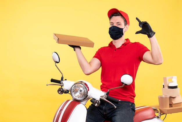 Mensageiro frontal masculino com máscara segurando a caixa de comida em amarelo