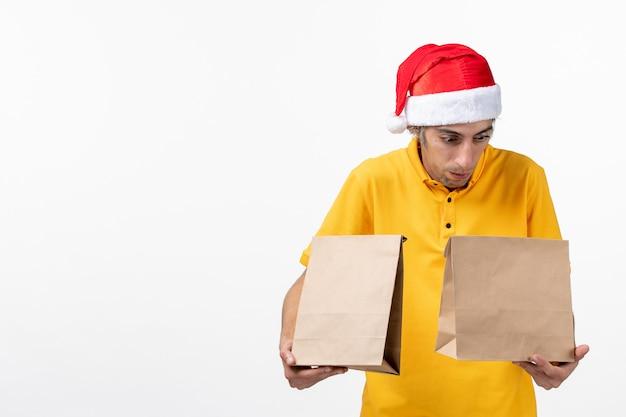 Mensageiro frontal masculino com pacotes de comida na mesa branca uniforme serviço serviço de refeição