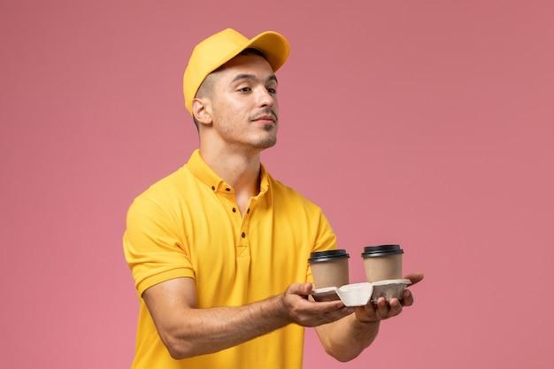 Mensageiro frontal masculino com uniforme amarelo entregando xícaras de café no fundo rosa claro