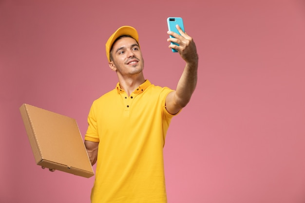 Mensageiro frontal masculino com uniforme amarelo tirando uma foto com a caixa de entrega de comida na mesa rosa