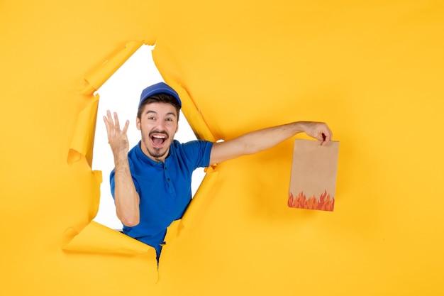 Mensageiro frontal masculino com uniforme azul dando pacote de comida no espaço amarelo