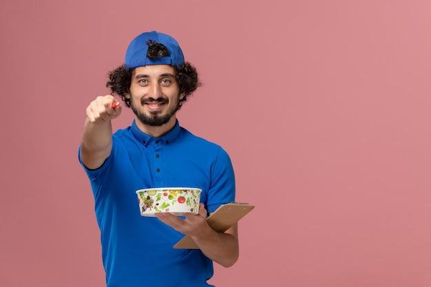 Mensageiro frontal masculino com uniforme azul e capa segurando um bloco de notas e uma tigela de entrega redonda na parede rosa