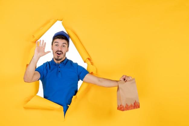Mensageiro frontal masculino com uniforme azul segurando um pacote de comida no espaço amarelo