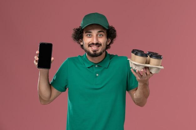 Mensageiro frontal masculino com uniforme verde e capa segurando xícaras de café com o telefone no trabalho de entrega uniforme de serviço de fundo rosa claro