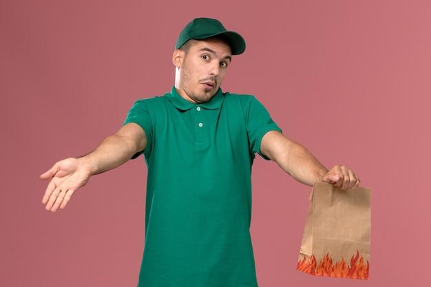 Mensageiro frontal masculino com uniforme verde segurando um pacote de comida em papel rosa claro