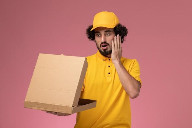 Mensageiro frontal masculino em uniforme amarelo segurando e abrindo a caixa de entrega de comida na parede rosa claro