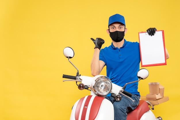 Mensageiro frontal masculino em uniforme azul com nota de arquivo na pandemia de serviço de entrega de vírus de trabalho secreto de bicicleta amarela
