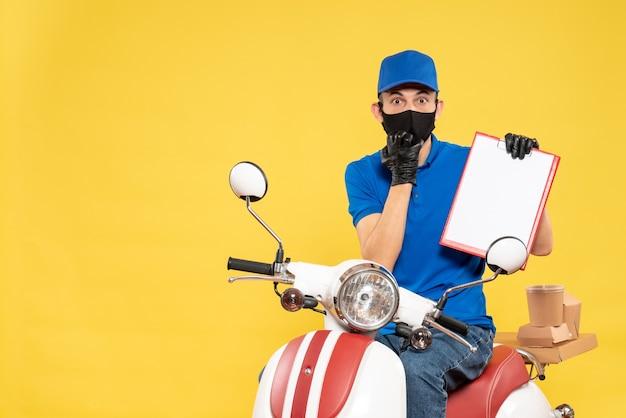 Mensageiro frontal masculino em uniforme azul com uma nota de arquivo sobre um vírus de pandemia de serviço de entrega de trabalho secreto de bicicleta amarela