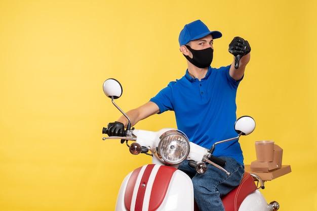 Mensageiro frontal masculino em uniforme azul e máscara descontente com o serviço de covidemia de trabalho amarelo - serviço de pandemia de entrega de bicicletas