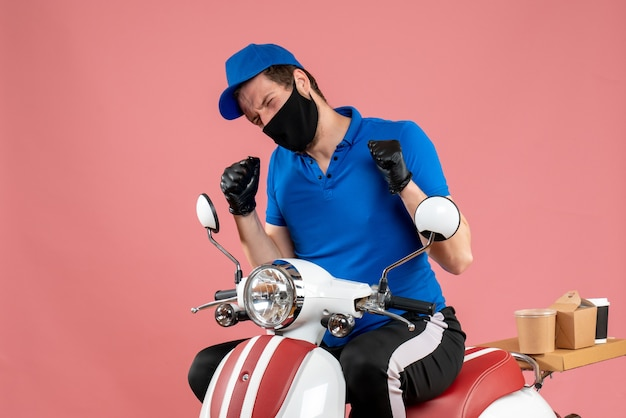 Mensageiro frontal masculino em uniforme azul e máscara em um serviço rosa fast-food covid- trabalho entrega vírus bicicleta cor