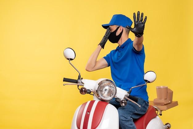 Mensageiro frontal masculino em uniforme azul e máscara no covid de trabalho de pandemia amarela - serviço de entrega de bicicletas de vírus
