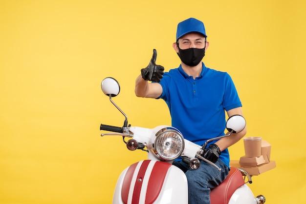 Mensageiro frontal sentado em uma bicicleta, mascarado em um covid de entrega de serviço de trabalho amarelo - pandemia de trabalho
