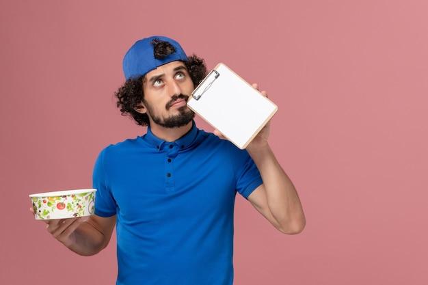 Mensageiro masculino com capa e uniforme azul, segurando o bloco de notas e a tigela de entrega redonda na parede rosa