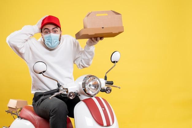Mensageiro masculino com máscara em bicicleta segurando caixa de comida em amarelo
