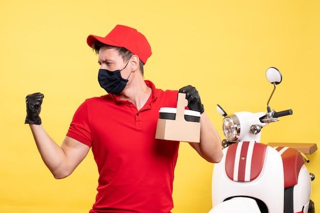 Mensageiro masculino com máscara preta e xícaras de café em um serviço de trabalho uniforme pandêmico de entrega de vírus de trabalho amarelo