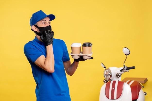 Mensageiro masculino com máscara preta segurando café em uniforme amarelo de serviço de pandemia de trabalho de entrega de trabalho covid