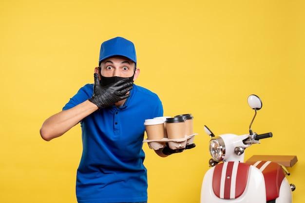 Mensageiro masculino com máscara preta segurando café em uniforme amarelo de serviço secreto de entrega de trabalho