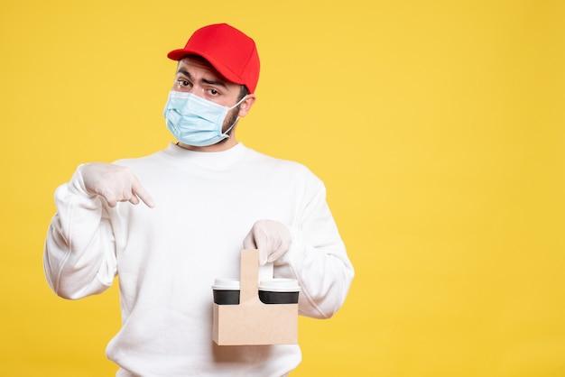 Mensageiro masculino com máscara segurando café em amarelo Foto gratuita