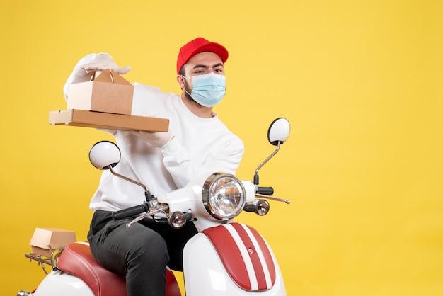 Mensageiro masculino com máscara segurando caixa de comida em amarelo