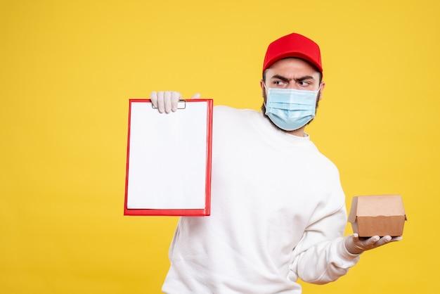 Mensageiro masculino com máscara segurando uma nota de arquivo e um pequeno pacote de comida em amarelo