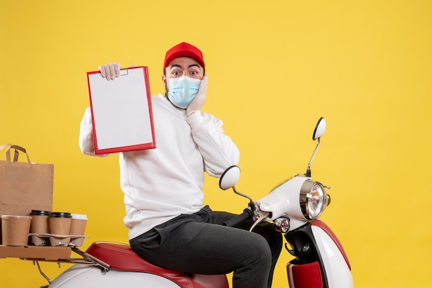 Mensageiro masculino com máscara segurando uma nota de arquivo em amarelo