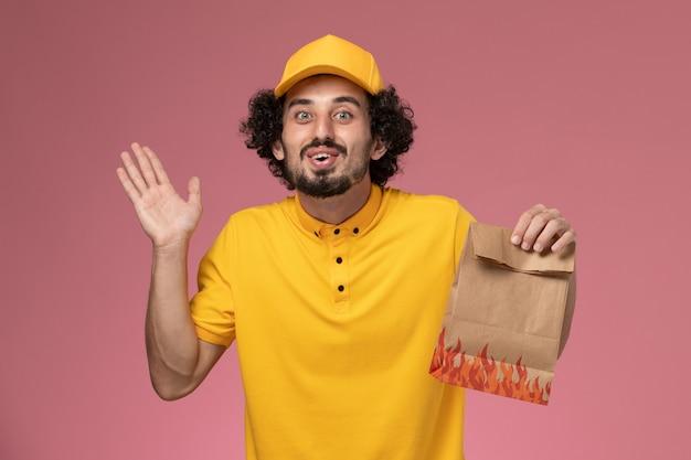 Mensageiro masculino com uniforme amarelo segurando um pacote de comida na parede rosa claro