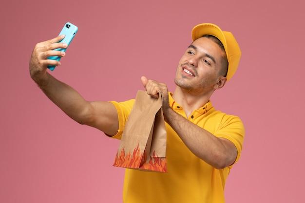 Mensageiro masculino com uniforme amarelo tira uma foto com um pacote de comida na mesa rosa