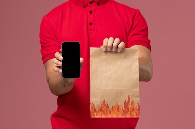 Mensageiro masculino com uniforme vermelho e capa segurando o pacote de comida e o telefone na parede rosa
