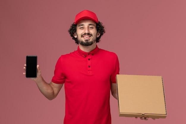 Mensageiro masculino de camisa vermelha e capa de frente segurando uma caixa de entrega de comida vazia com o telefone na parede rosa