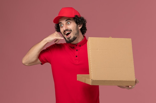 Mensageiro masculino de camisa vermelha e capa segurando a caixa de entrega de comida na parede rosa claro de frente