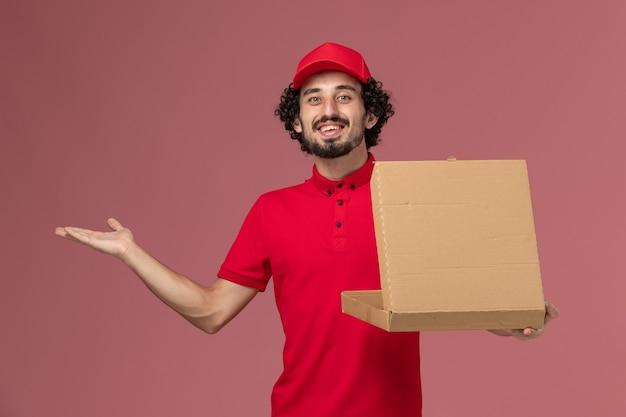 Mensageiro masculino de camisa vermelha e capa segurando a caixa de entrega de comida na parede rosa