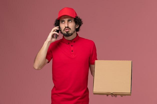 Mensageiro masculino de camisa vermelha e capa segurando a caixa de entrega de comida vazia enquanto fala ao telefone na mesa rosa da empresa de uniforme de entrega de serviço
