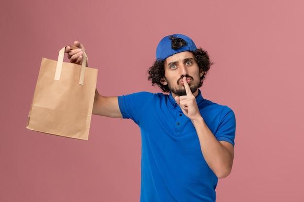 Mensageiro masculino de frente com uniforme azul e capa segurando um pacote de comida de papel de entrega em uniforme de serviço de trabalho de entrega de parede rosa