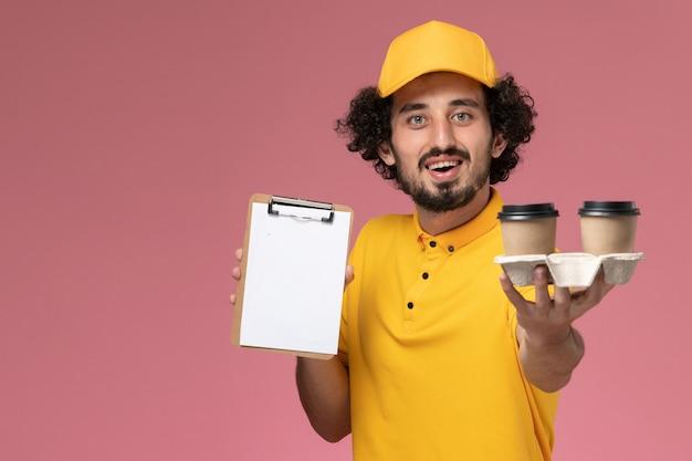Mensageiro masculino de uniforme amarelo e capa segurando xícaras de café marrons e um bloco de notas na parede rosa