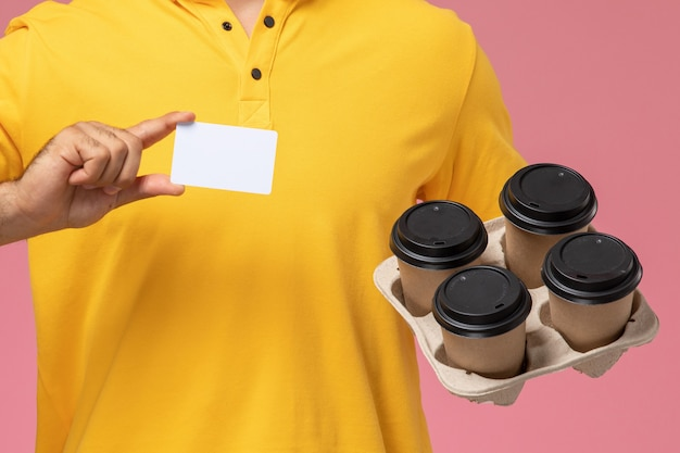 Mensageiro masculino de uniforme amarelo segurando um cartão de plástico e entregando xícaras de café em fundo rosa