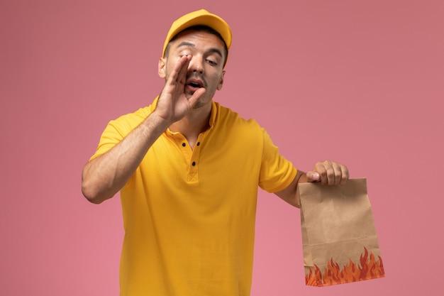 Mensageiro masculino de uniforme amarelo segurando um pacote de comida sussurrando no fundo rosa