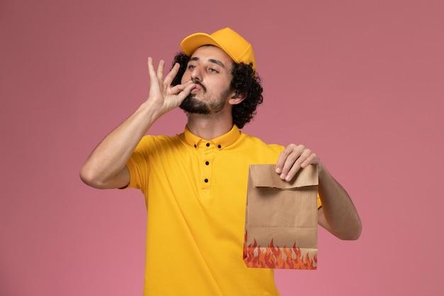 Mensageiro masculino de uniforme amarelo segurando um pacote de papel para comida mostrando uma placa saborosa na parede rosa claro