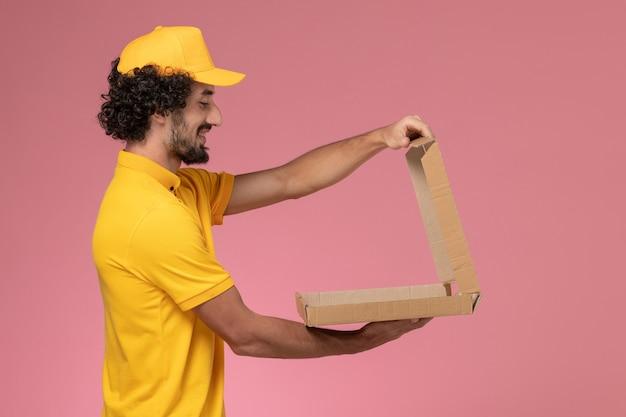 Mensageiro masculino de uniforme amarelo segurando uma caixa de comida na parede rosa claro