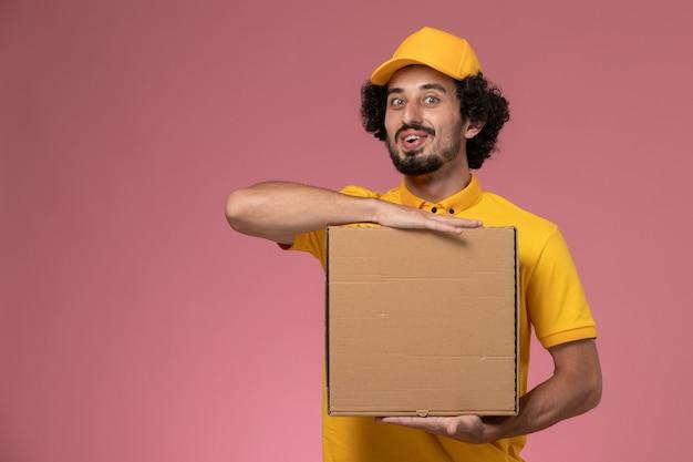Mensageiro masculino de uniforme amarelo segurando uma caixa de entrega de comida na parede rosa claro