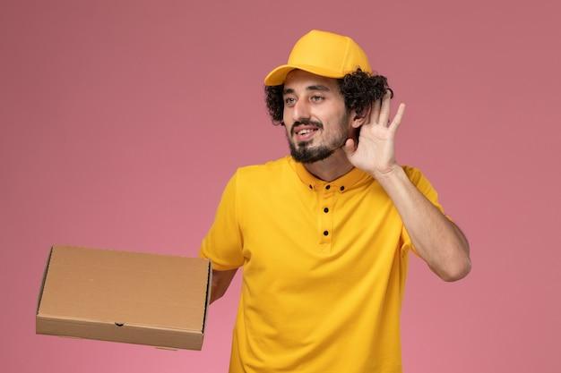 Mensageiro masculino de uniforme amarelo segurando uma caixa de entrega de comida tentando ouvir na parede rosa claro