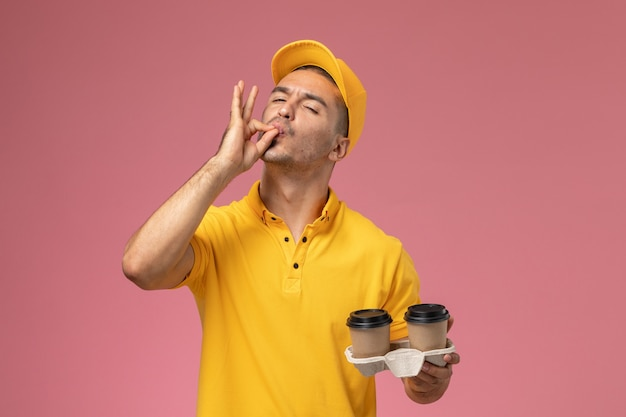 Mensageiro masculino de uniforme amarelo segurando xícaras de café de entrega mostrando uma placa saborosa em fundo rosa claro.