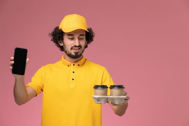 Mensageiro masculino de uniforme amarelo segurando xícaras de café marrons com o telefone na parede rosa