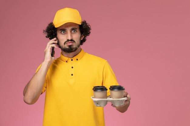 Mensageiro masculino de uniforme amarelo segurando xícaras de café marrons e falando ao telefone na parede rosa
