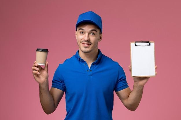 Mensageiro masculino de uniforme azul segurando a xícara de café com bloco de notas rosa, serviço de uniforme de trabalho