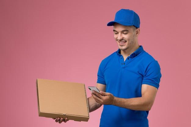 Mensageiro masculino de uniforme azul segurando caixa de comida de entrega e smartphone rosa, uniforme de trabalho.