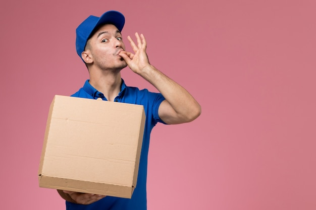 Mensageiro masculino de uniforme azul segurando caixa de comida posando na rosa