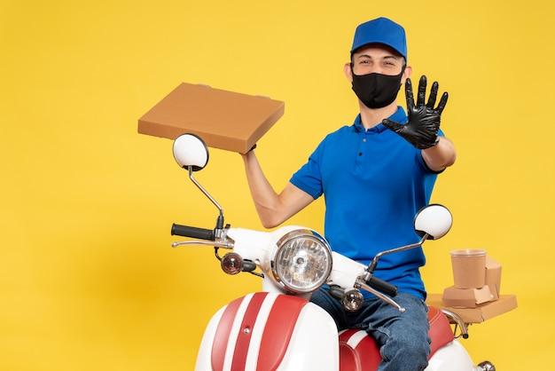 Mensageiro masculino de uniforme azul segurando uma caixa de comida na pandemia de vírus amarelo entrega covid entrega trabalho serviço bicicleta