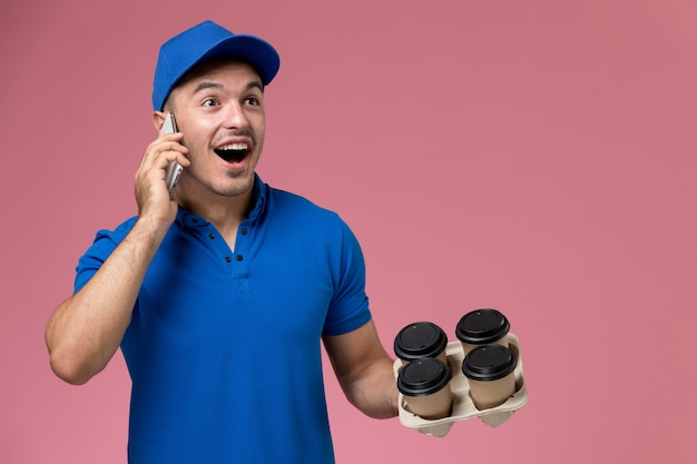 Mensageiro masculino de uniforme azul segurando xícaras de café de entrega falando no telefone na rosa, entrega de emprego de serviço uniforme