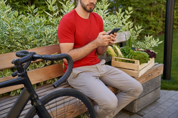 Mensageiro masculino de uniforme sentado no banco ao ar livre e usando