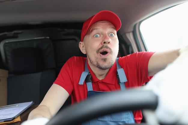 Mensageiro masculino de uniforme surpreso dirigindo um carro